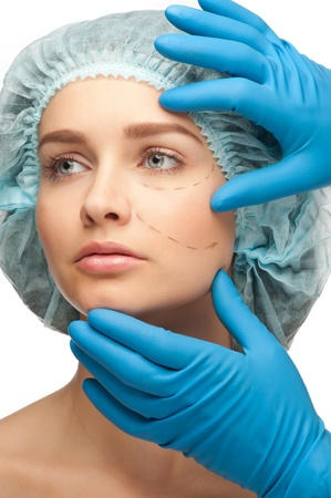 Beautiful young woman with perforation lines on her face before plastic surgery operation. Beautician touching woman face. Stock Photo - 10997953