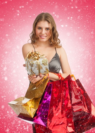 Woman shopping for christmas gifts. Happy young caucasian woman with gift and shopping bags. Stock Photo - 11375082