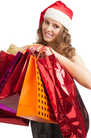 Woman shopping for christmas gifts. Happy young woman in santa hat with shopping bags . Stock Photo - 11375090
