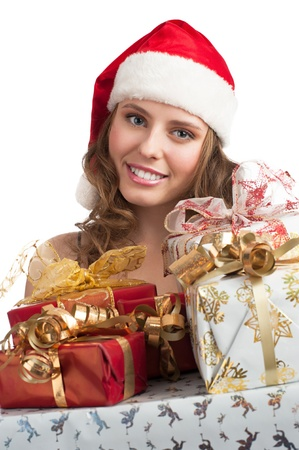 Woman shopping for christmas. Happy young woman in santa hat with gifts.  photo