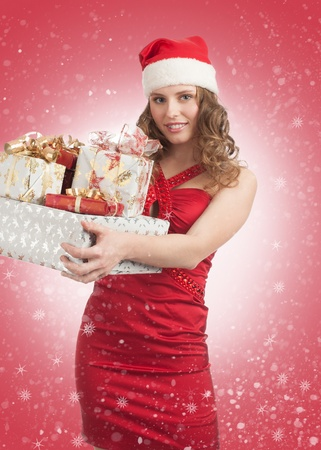 Woman shopping for christmas. Happy young woman in red dress and santa hat with gifts.  photo