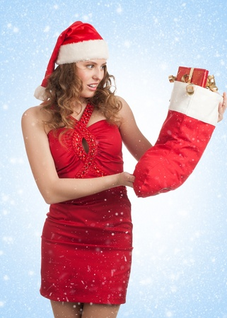 Woman shopping for christmas. Happy young woman in red dress and santa hat holding christmas socks with gifts.  photo