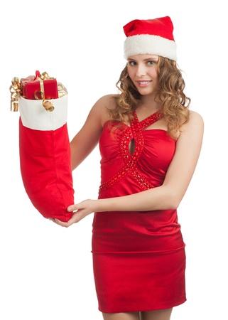 señora: Mujer de compras para la Navidad. Mujer joven feliz en el vestido rojo y sombrero de santa celebración de calcetines de Navidad con regalos. Foto de archivo