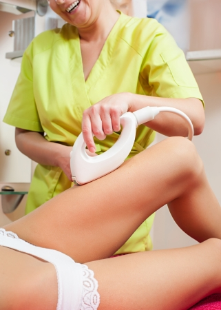 Young woman getting radio frequency cellulite treatment in spa salon photo
