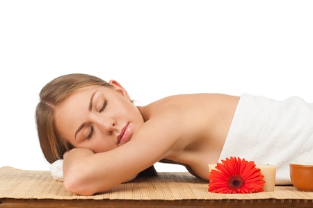 Portrait of young beautiful spa woman with closed eyes lying on bamboo mat at spa salon  photo
