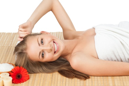 Portrait of young beautiful spa woman lying on bamboo mat at spa salon Stock Photo - 11375002