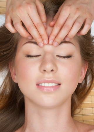 Portrait of young beautiful woman receiving facial massage at spa salon  photo