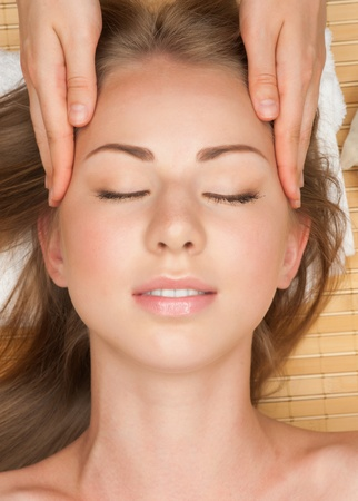head massage: Portrait of young beautiful woman receiving facial massage at spa salon