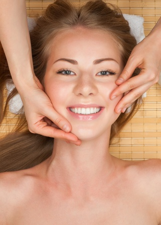 face massage: Portrait of young beautiful woman receiving facial massage at spa salon