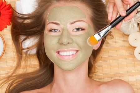 pulizia viso: Primo piano di giovane donna bella, con maschera di argilla facciale, presso il salone spa