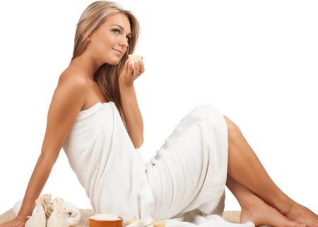 Portrait of young beautiful spa woman sitting on bamboo mat at spa salon photo