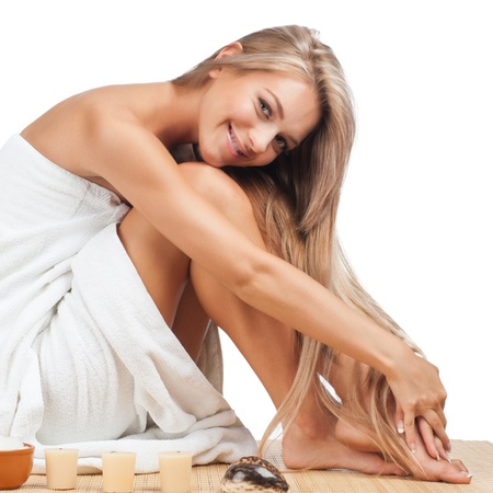 woman in towel: Portrait of young beautiful spa woman sitting on bamboo mat at spa salon