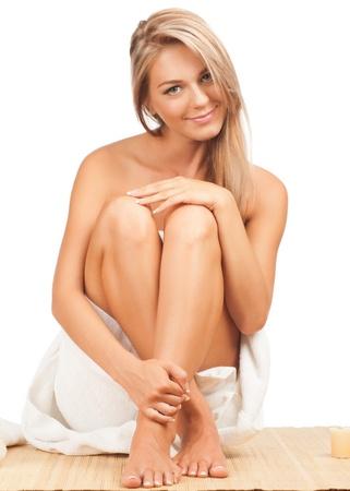 benen: Portret van jonge mooie spa vrouw zit op bamboe mat op spa salon