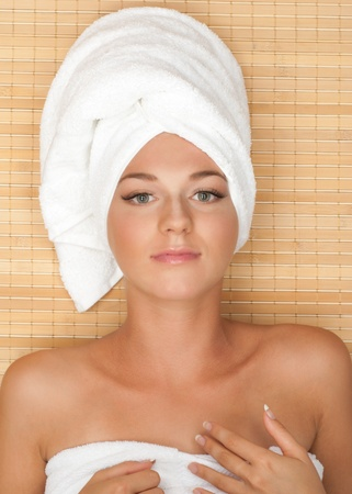 Young beautiful spa woman with a towel around her head lying at spa salon photo
