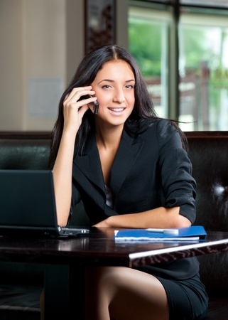 Young attractive business woman working on her laptop and talking on the phone in a cafe Stock Photo - 11375079