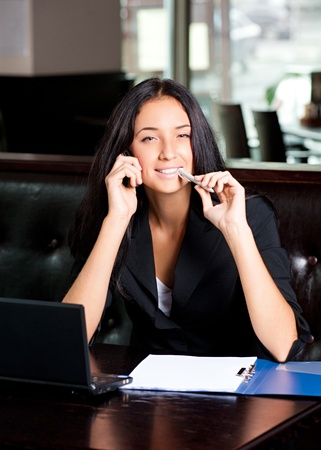 Young attractive business woman working on her laptop and talking on the phone in a cafe photo