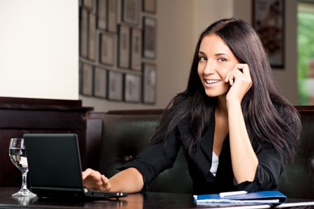 Young attractive business woman working on her laptop and talking on the phone in a cafe Stock Photo - 11375092