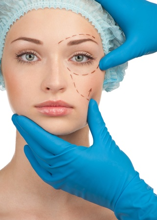 Beautiful young woman with perforation lines on her face before plastic surgery operation. Beautician touching woman face. Stock Photo