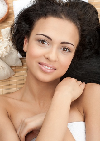 Portrait of young beautiful spa woman lying on bamboo mat at spa salon photo