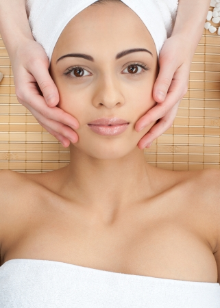 hand towel: Portrait of young beautiful woman receiving facial massage at spa salon