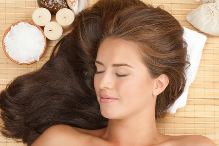 Close-up portrait of young beautiful spa woman with long brown hair lying on bamboo mat at spa salon photo