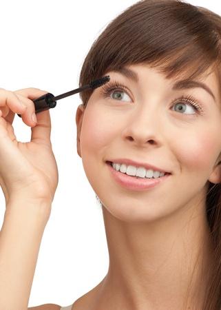 Beautiful woman applying mascara on her eyelashes, isolated on white background Stock Photo - 11378288