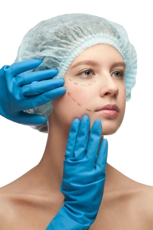 Beautiful young woman with perforation lines on her face before plastic surgery operation. Beautician touching woman face. Stock Photo - 11378247