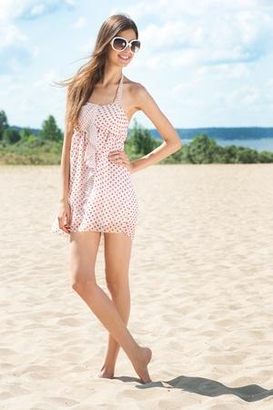 Jeune femme belle dans la robe d'été et lunettes de soleil sur la plage
