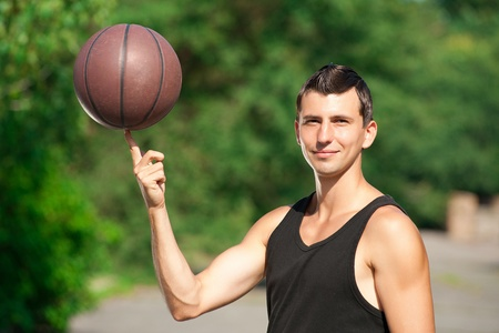 Young basketball player spinning basketball on his finger outdoors photo