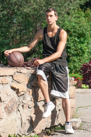 Young basketball player sitting and holding a basketball  photo
