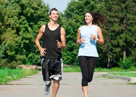 ジョグ: 男と女の公園でジョギングの若いフィットネス カップル