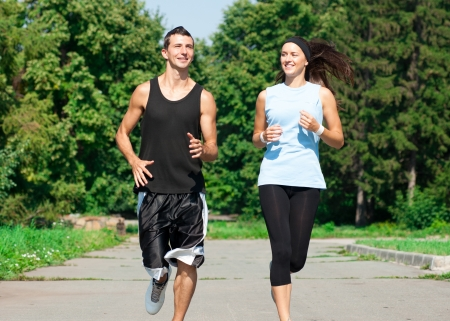 summer sport: Young fitness couple of man and woman jogging in park