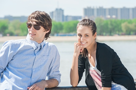Young beautiful couple walking together in city in sunny summer day  photo