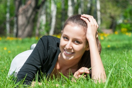 Portrait of beautiful young woman lying on grass in park and smiling photo