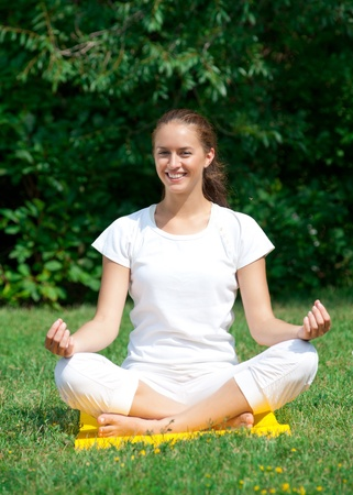 Young beautiful woman sitting with crossed legs and doing yoga meditation in park  photo