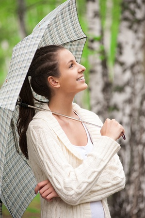 Young beautiful woman with umbrella walking in park Stock Photo - 11380015
