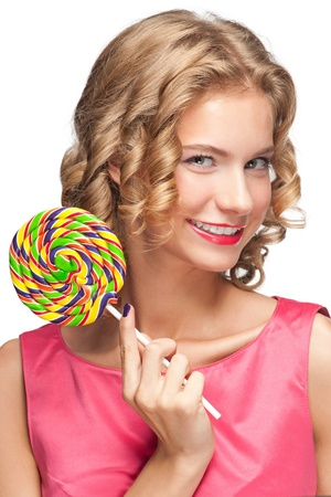 Portrait of beautiful girl with blond curly hair holding lollipop photo