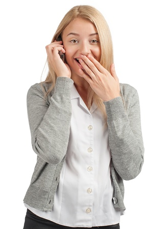 Surprised business woman talking on a cell phone and covering her mouth by the hand photo