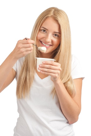 Young beautiful woman in white t-shirt eating yogurt as breakfast or snack. Isolated on white photo