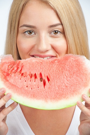 Close-up of young beautiful woman with long blond hair eating fresh watermelon photo