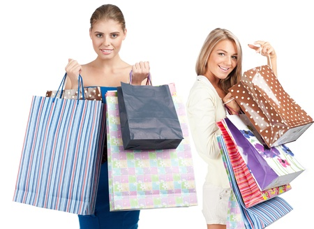 Two happy young women with colorful shopping bags. Isolated on white background photo