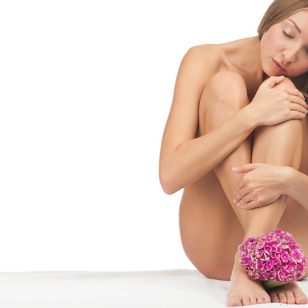 Beautiful naked woman sitting with flower between her legs on white sheet. Isolated on white background Stock Photo