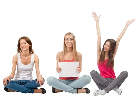 Three happy young women with blank signboard sitting with crossed legs, isolated on white background photo