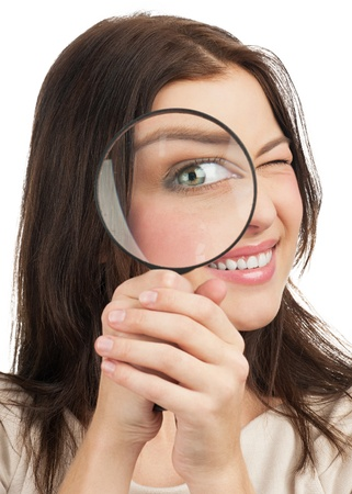 Pretty young woman looking through a magnifying glass. Isolated on white background photo