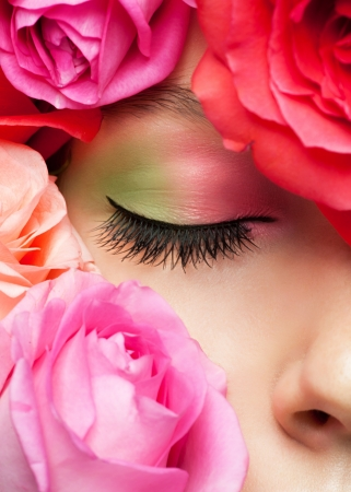 Close-up of closed female eye with bright stylish makeup surrounded by roses Stock Photo