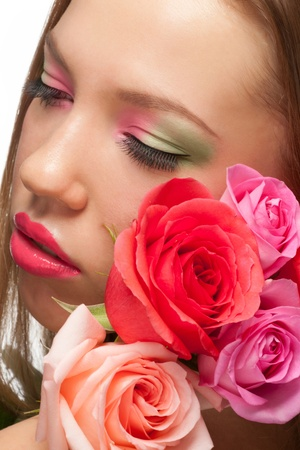 Close-up portrait of young beautiful woman with bright stylish make-up and roses. photo