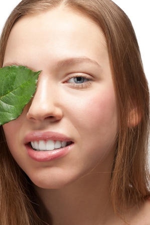 Close-up portrait of young beautiful woman covering her eye by green leaf and smiling, over white background Stock Photo - 11742213