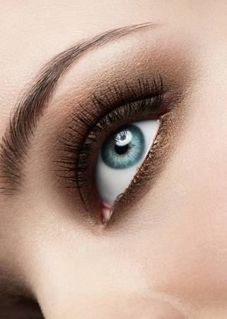 Close-up shot of beautiful female blue eye with bright fashion make-up