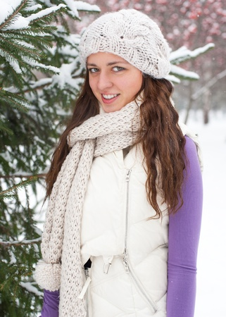 Young beautiful woman behind snow tree in winter park photo