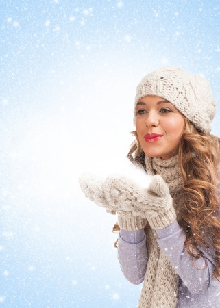 Christmas woman blowing snow, against blue background photo
